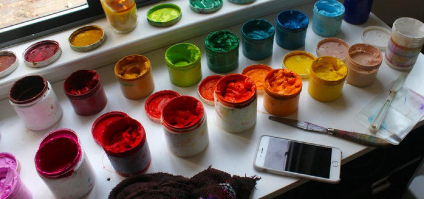 Brightly colored paints and a cell phone on a table