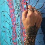 Photo of a hand with tattoos holding a paintbrush up to a blue painting, for The Big Ask