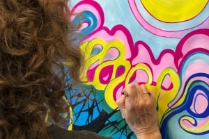 Woman working on brightly colored process painting