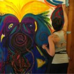 A woman working on a large process painting at Breitenbush Hot Springs.