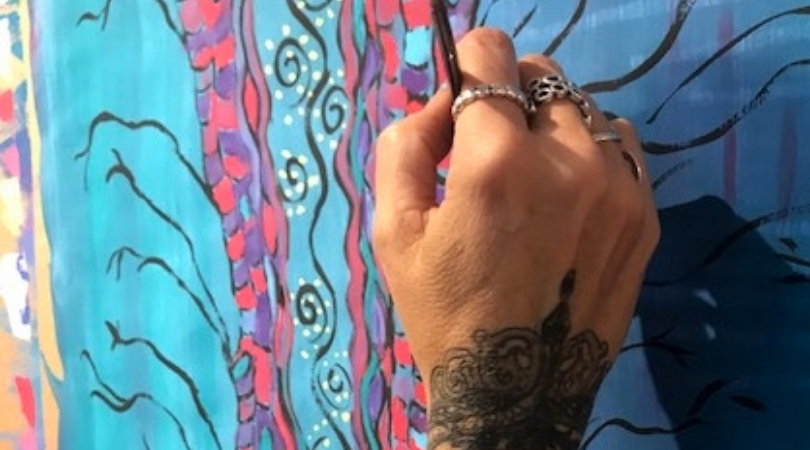 Photo of a hand with tattoos holding a paintbrush up to a blue painting (The Big Ask)