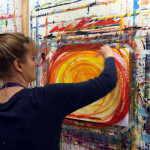 Photo of woman painting bright orange, yellow, and red sprials (Episode 6 of The Painting Experience Podcast: Following the Energy)