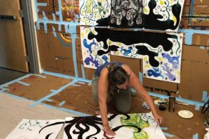 Woman working on large process painting at Encino Painting Experience workshop